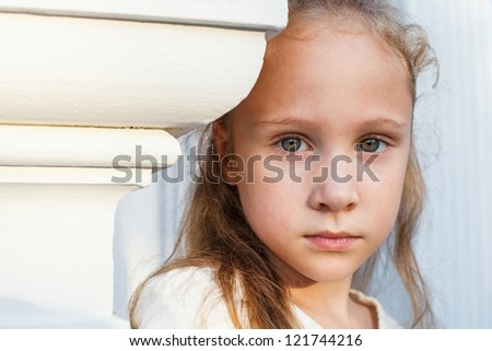 sad little girl on the background of an white wall - stock photo