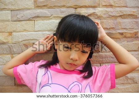 Sad little girl on the brick wall - stock photo