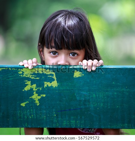 Sad little girl sits on bench at park - stock photo