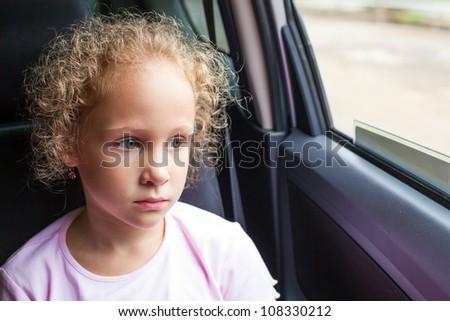 sad little girl sitting in the car near the window - stock photo