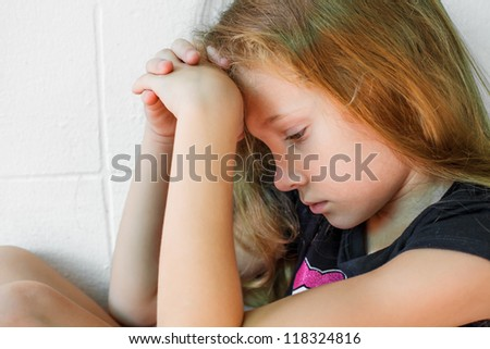 sad little girl sitting near the wall - stock photo