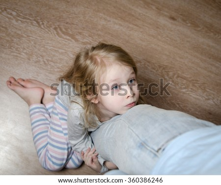 Sad little girl sitting on the floor and hugging her father's leg, top view