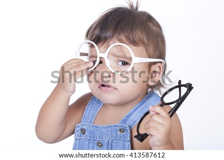 Sad little girl trying on pair of white glasses while holding black ones.Isolated - stock photo