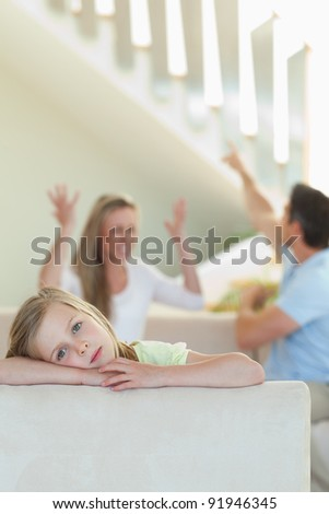 Sad little girl with her fighting parents behind her - stock photo