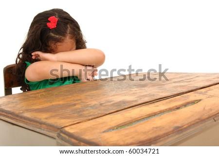 Sad little three year old hispanic girl sitting in big desk over white background. - stock photo