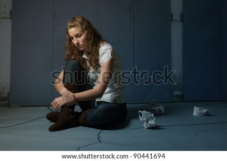 Sad lone orphan girl sitting on flor in darkness - stock photo