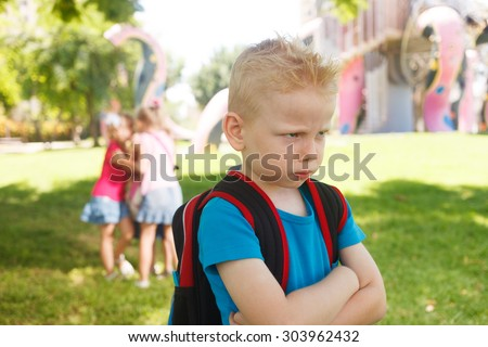 Sad lonely child being bullied by children