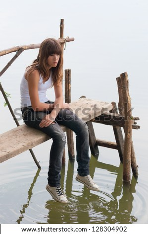 Sad lonely teenage girl sitting on the small wooden dock on the river. - stock photo