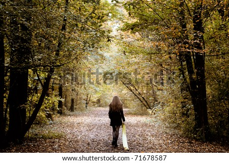 Sad lonely woman walking alone into the woods - stock photo