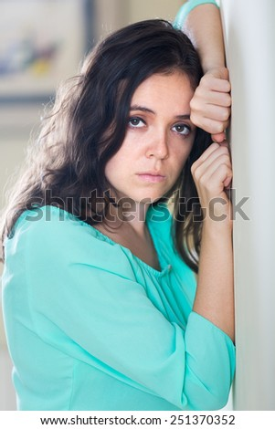 Sad lonely young long-haired woman crying at home - stock photo