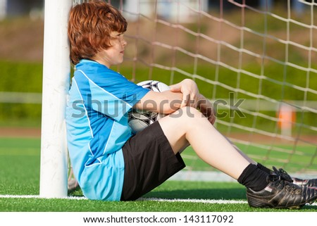 sad looking boy leaning at goal on soccer field - stock photo
