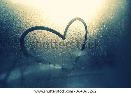 Sad love heart symbol drawn by hand on the wet, frozen and dirty window glass with sunlight in blue background. Selective focus used. - stock photo