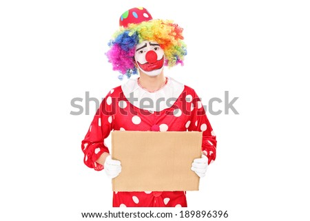 Sad male clown holding a blank carton sign isolated on white background