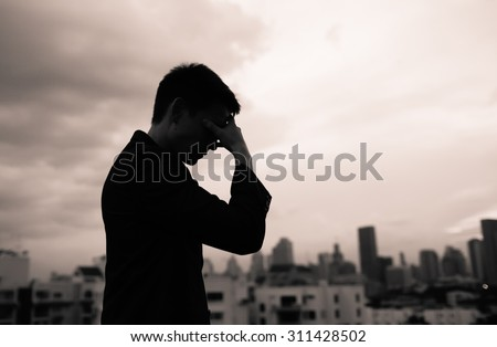 Sad male in the city with dark clouds in the sky.  - stock photo