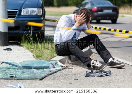 Sad man at road accident scene, horizontal - stock photo