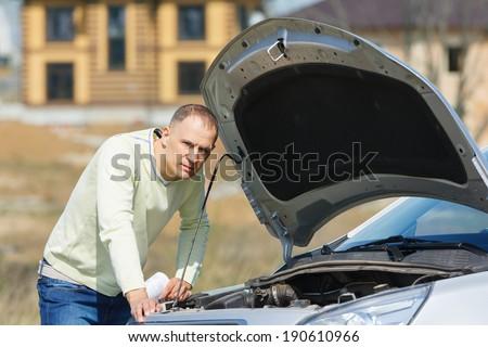 sad man had broken open the hood of the car - stock photo
