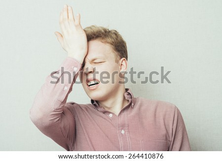 Sad man holding his forehead with his hand - stock photo