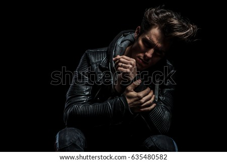 sad man in leather jacket holding his hand while sitting on chair on black background