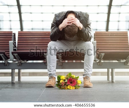 Sad man is sitting alone at the train station with his head down - stock photo
