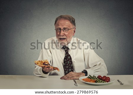 Sad man looking at pizza tired of salad diet