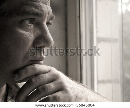Sad man looking out the window