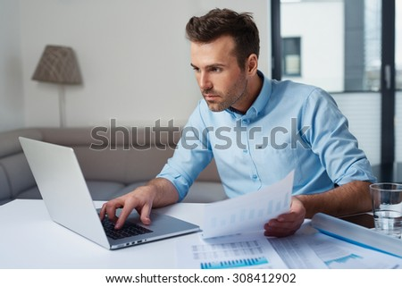 Sad man paying bills on his laptop - stock photo