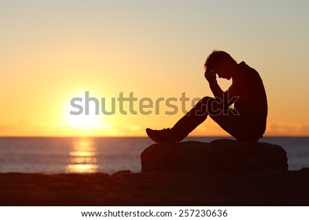 Sad man silhouette worried on the beach at sunset with the sun in the background - stock photo