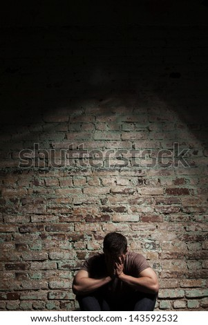 Sad man sitting alone against brick wall. - stock photo