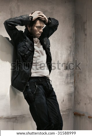 Sad man standing at wall - stock photo