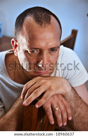 Sad man thinking with head on hands - stock photo