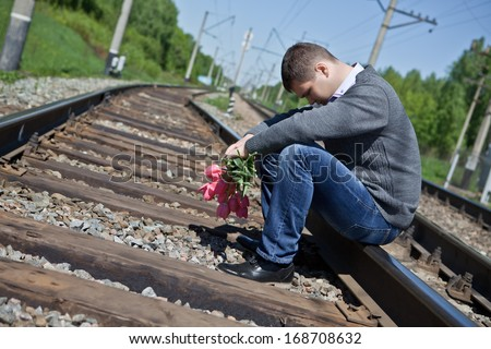 Sad man with flowers sitting on the rails - stock photo