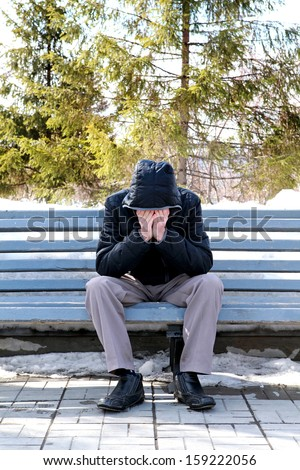 Sad Man with Hide Face on the Bench at the winter park - stock photo