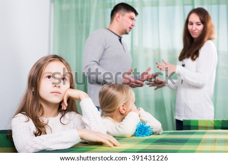 Sad man with wife and two unhappy children after quarrel in home - stock photo