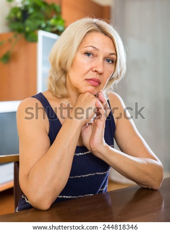 Sad mature  adult woman sitting near table  - stock photo