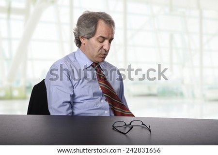 sad  mature business man on a desk at the office - stock photo