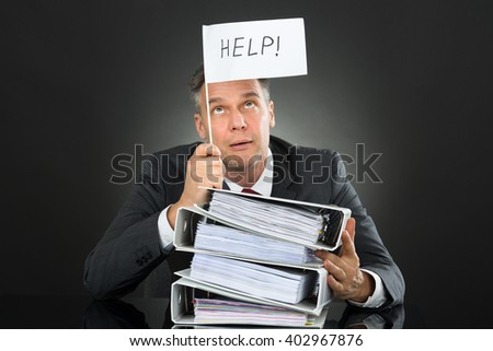 Sad Mature Businessman Holding Flag With Help Text Above Stack Of Folders On Desk - stock photo