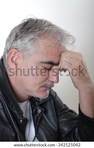 Sad mature man with closed eyes and hand at his forehead