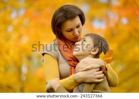 Sad mother with a son on a walk during the fall of the leaves in the park - stock photo