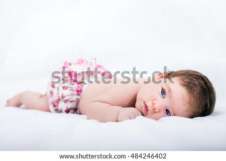 Sad newborn baby with beautiful blue eyes lying on white bed