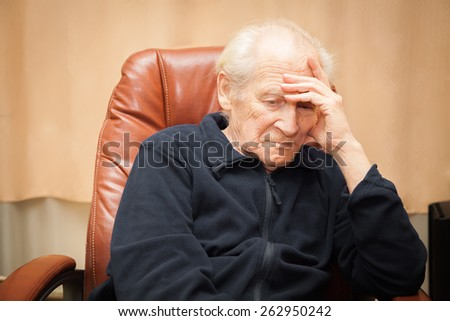 sad old man with a hand on his forehead - stock photo