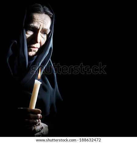 Sad old woman Senior woman in sorrow with candle depressed portrait - stock photo
