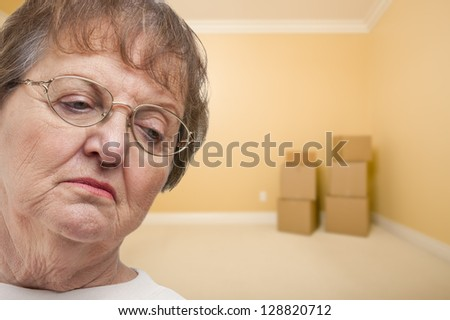 Sad Older Woman In Empty Room with Boxes - Concept for Foreclosure, Divorce, Moving, etc. - stock photo