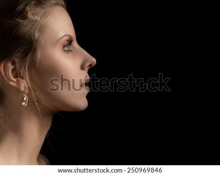 sad pensive female profile on black background - stock photo