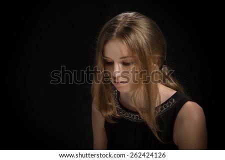 sad pensive girl thinking on black background - stock photo