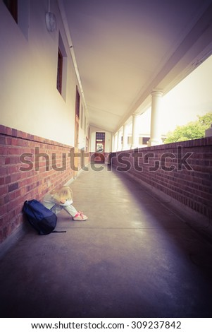Sad pupil sitting alone on ground at corridor - stock photo