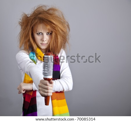 Sad red-haired girl with comb. - stock photo