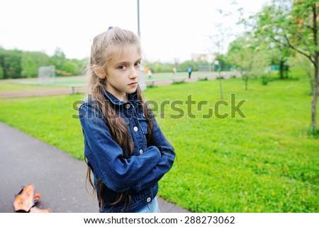 Sad school aged girl on the school yard - stock photo