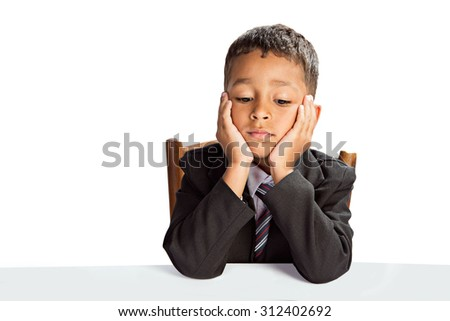 Sad schoolboy sitting at the desk and thinking. - stock photo