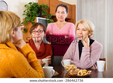 sad senior female friends  problems at table  - stock photo