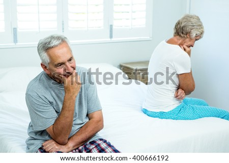 Sad senior man and woman sitting on bed at home - stock photo